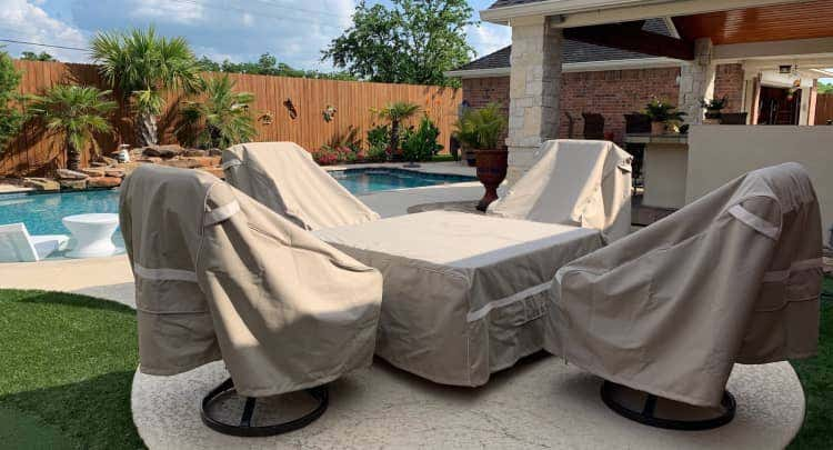 Table and chairs with Prestige covers in a backyard by a pool