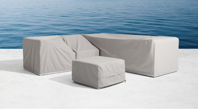 Outdoor sectional and ottoman with grey covers near a body of water